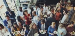 Grupo de personas cenando de pie en restaurante